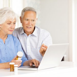 Senior couple with pill bottles browsing internet on laptop at home. Horizontal shot.